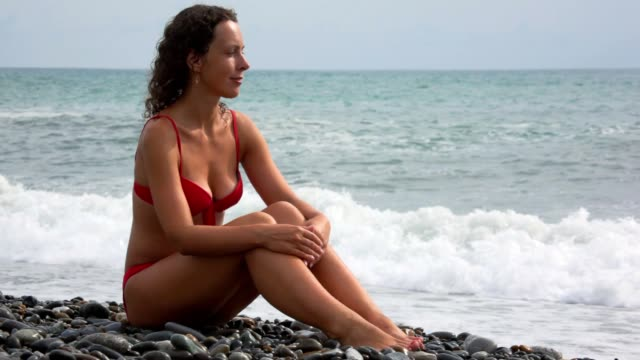Woman sits on beach and looks at surfing wave video