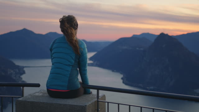 Woman sits on edge railing overlooking sunset and view of lake and mountains below