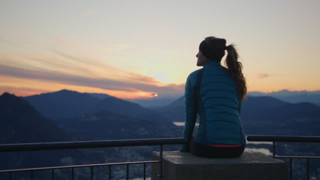 stockvideo's en b-roll-footage met vrouw zit op balustrade met uitzicht op zonsondergang en uitzicht op het meer en de bergen beneden - mid volwassen vrouw