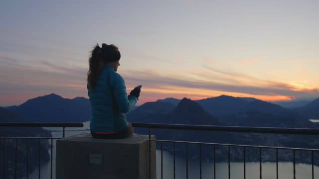 woman sits on top of mountain at sunset using smartphone - grandangolo tecnica fotografica video stock e b–roll