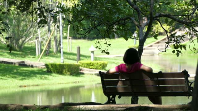 woman sitting alone in garden - penombra video stock e b–roll