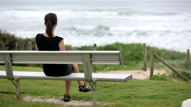 Woman Sitting Alone on Bench and Looking the sea, Australia DSLR video of Woman Sitting Alone on Bench and Looking the sea, Australia on a rainy day. park bench stock videos & royalty-free footage