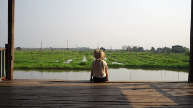woman sitting and looking at floating gardens on inle lake - myanmar video stock e b–roll