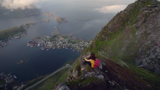 vídeos de stock e filmes b-roll de woman sitting and looking from reinebringen mountain on lofoten island - reine