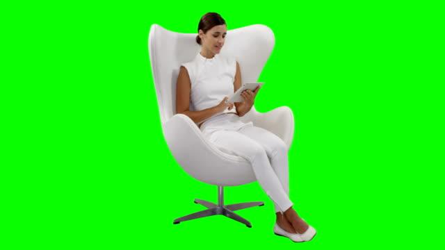 여 자가 앉아 디지털 태블릿을 사용 하 여 - 앉음 스톡 비디오 및 b-롤 화면