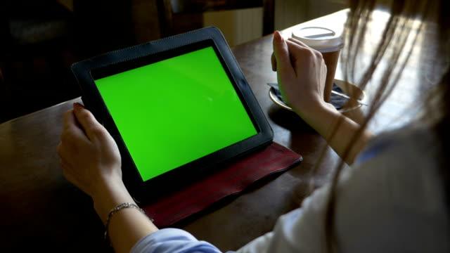 frau sitzt an einem tisch green-screen-tablet-pc verwenden und die in- und out-gesten in einem café vergrößern - tablet mit displayinhalt stock-videos und b-roll-filmmaterial