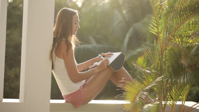 Woman sitting at balcony and writing in diary with garden on the background video