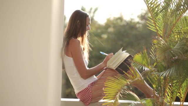 kvinnan sitter på balkongen och skriva i dagboken med trädgård på bakgrunden - linjerat papper bakgrund bildbanksvideor och videomaterial från bakom kulisserna