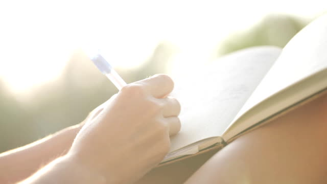 kvinnan sitter på balkongen och skriva i dagboken med trädgård på bakgrunden - anteckningsblock bildbanksvideor och videomaterial från bakom kulisserna
