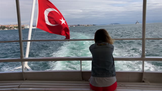 woman sitting behind the boat with turkish flag - cultura turca video stock e b–roll