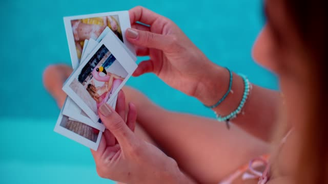 woman sitting by pool looking at summer holidays polaroids - foto video stock e b–roll