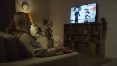 Woman Sitting Down on Couch and Watching TV in Evening Medium shot of woman walking into dark living room and sitting down on couch to watch TV in evening advertisement stock videos & royalty-free footage
