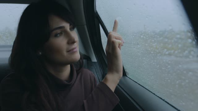 Woman sitting in a car at rainy day drawing heart on window video