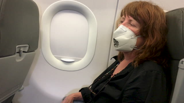 vídeos de stock e filmes b-roll de woman sitting in an airplane seat wearing a n95 face mask - covid flight