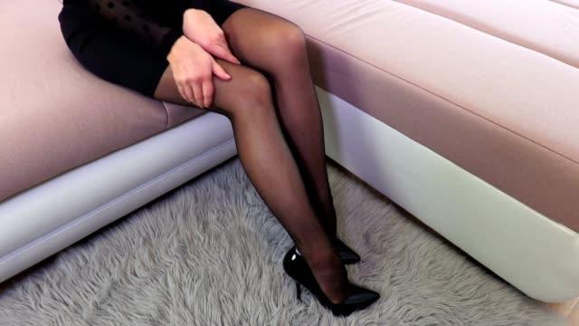 Mujer sentada en la cama y tocar medias negro - vídeo