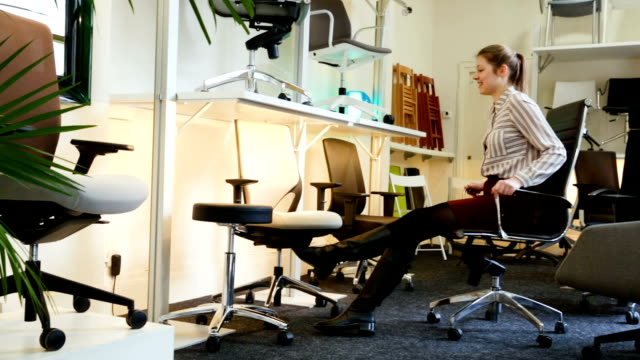 woman sitting in ergonomic office chair Satisfied young woman sitting in ergonomic office chair in furniture store before buying furniture stock videos & royalty-free footage