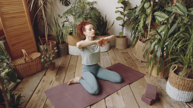 woman sitting in hero pose and stretching arms up during yoga practice - postawa filmów i materiałów b-roll