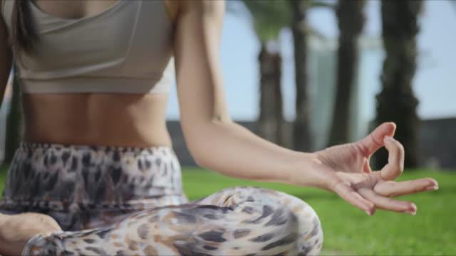 vídeos de stock e filmes b-roll de woman sitting in lotus pose in park. fit girl showing gyan mudra outdoors - membro