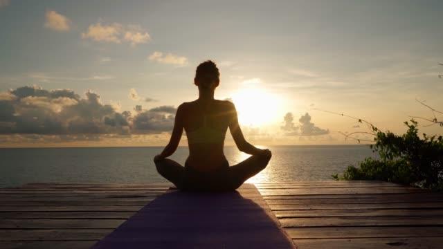 vídeos de stock e filmes b-roll de woman sitting in lotus position - budismo