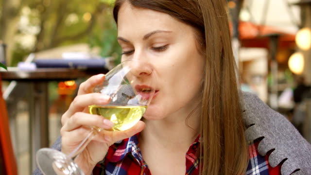Woman sitting in street cafe drinking white wine from glass. Smiling thirsty female at restaurant video