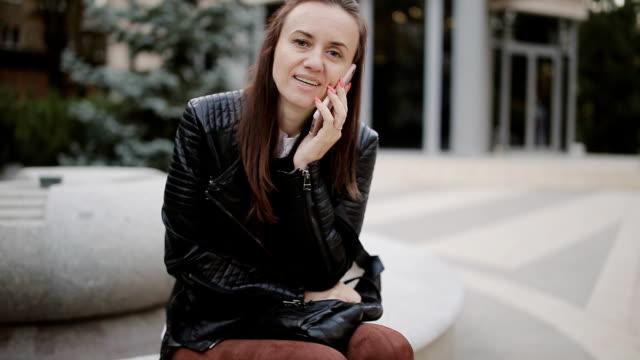 vidéos et rushes de une femme assise dans l'entreprise de construction et de parler au téléphone. portrait urbain. - extérieurs d écoles