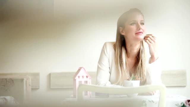 donna seduta nella caffetteria sorridente - blazer video stock e b–roll