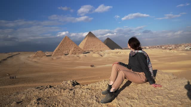 Woman sitting in the desert near the Giza pyramids