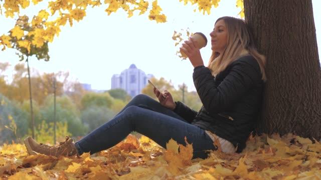 vídeos y material grabado en eventos de stock de mujer sentada cerca de árbol en hojas de otoño amarillo, utiliza aplicaciones y tomando café - moda de otoño