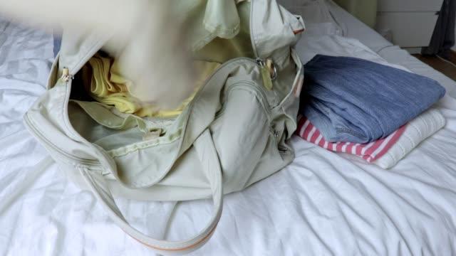 Mujer sentada en una cama y poner la ropa en una bolsa de laggage, preparación para el viaje y viaje - vídeo