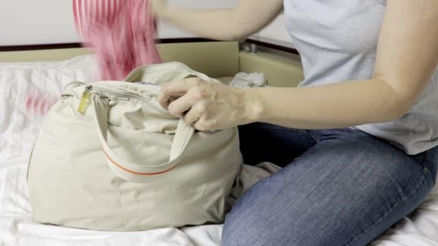 Mujer sentada en una cama, se abre una bolsa y teniendo ropa de una bolsa de laggage - vídeo