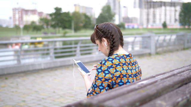 woman sitting on a bench in the park and listening to music from your phone video