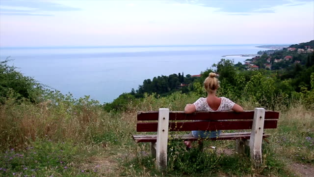 woman sitting on a bench looking at the sea - садовая скамья стоковые видео и кадры b-roll