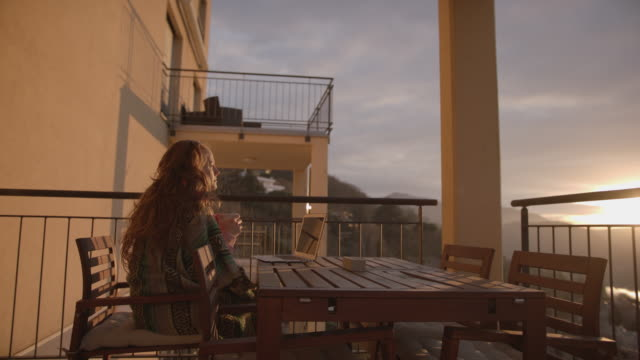 Woman sitting on balcony under blanket working on computer Enjoying sunset on balcony at home blanket stock videos & royalty-free footage