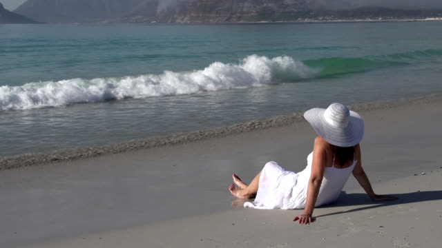 Woman sitting on beach looking out to sea, Cape Town,South Africa video