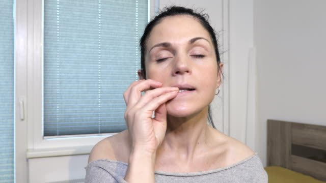 woman sitting on bed and biting nails - ноготь на руке стоковые видео и кадры b-roll