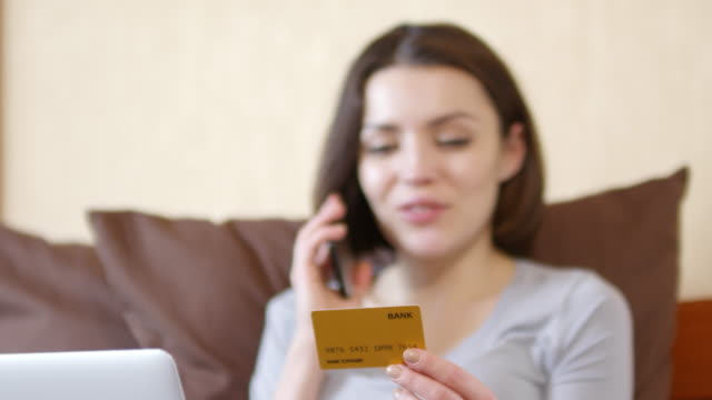 woman sitting on bed and telling credit card number over phone - credit card filmów i materiałów b-roll