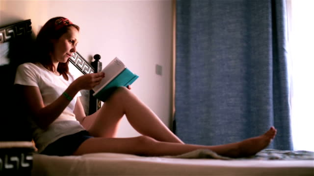 Woman sitting on bed making notes to her diary video