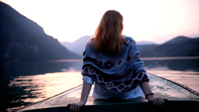 Woman sitting on boat prow in sunset