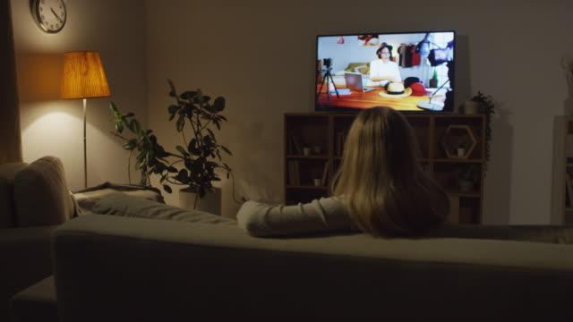 vídeos y material grabado en eventos de stock de mujer sentada en couch y cambiando los canales de tv - mirar la televisión
