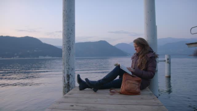kvinna sitter på docka läser bok vid solnedgången, har ögonblick ensam - läder bildbanksvideor och videomaterial från bakom kulisserna