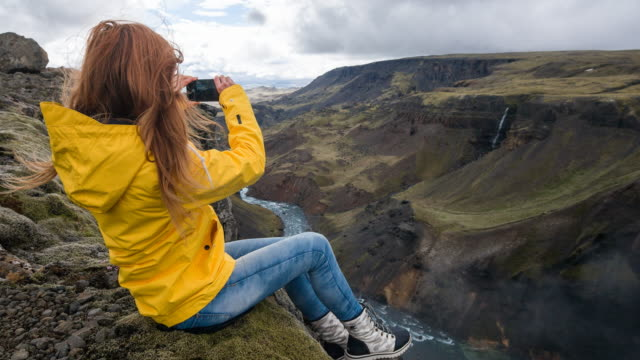 Woman sitting on edge of a canyon, taking pictures of breathtaking view