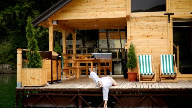 Woman sitting on log cabin pier - balcony
