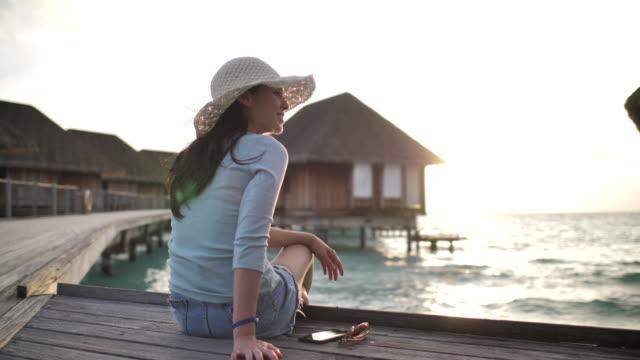 woman sitting on resort and enjoying view at sunset - вилла стоковые видео и кадры b-roll