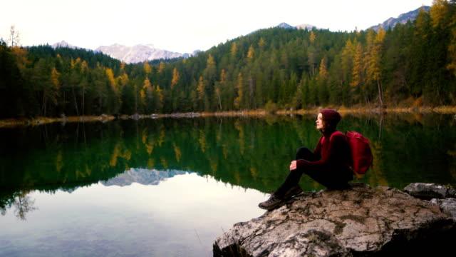 바위에 앉아서 알프스에서 eibsee 호수의 풍경을 보고 여자 - mountain top 스톡 비디오 및 b-롤 화면