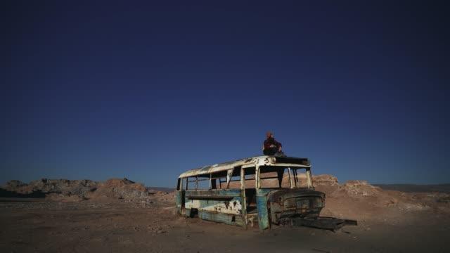 stockvideo's en b-roll-footage met de zitting van de vrouw op dak van verlaten bus in de woestijn van atacama - maasvallei