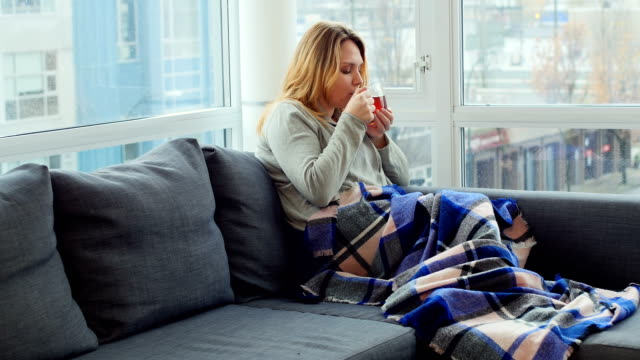 Woman sitting on sofa holding cup of coffee video