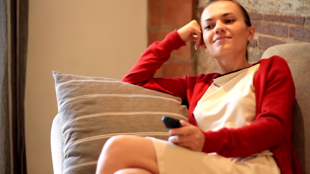 Woman sitting on sofa with a tv remote control video
