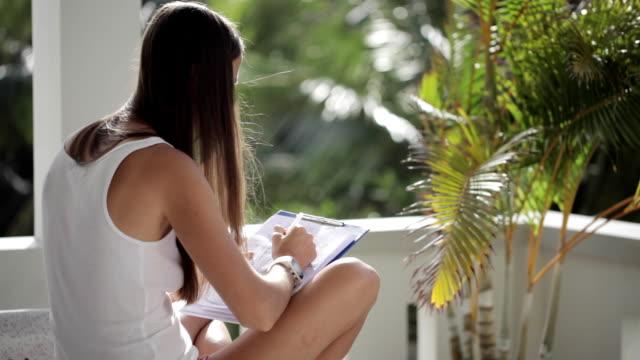 kvinnan sitter på balkongen och spenderar tid på ritning med ballpen på papper - linjerat papper bakgrund bildbanksvideor och videomaterial från bakom kulisserna