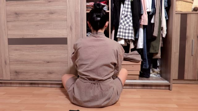 Woman sitting on the floor near wardrobe and choosing clothes Woman sitting on the floor near wardrobe and choosing clothes cabinet stock videos & royalty-free footage