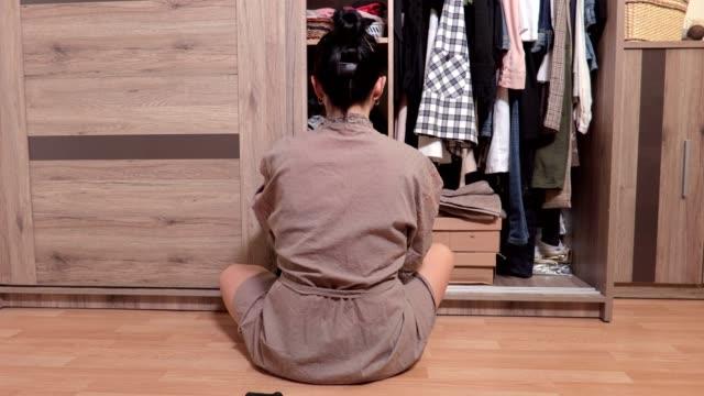 kvinnan sitter på golvet nära garderob och välja kläder - looking inside inside cabinet bildbanksvideor och videomaterial från bakom kulisserna